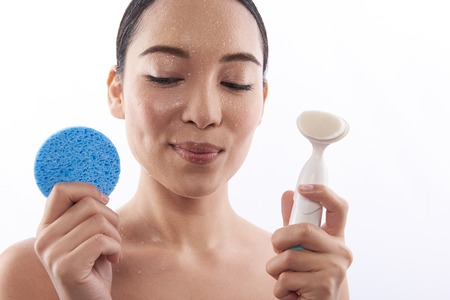 Asian lady smiling and holding two cosmetic sponges Reklamní fotografie