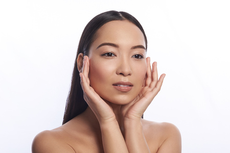 Calm Asian woman touching her face with two hands Stock Photo