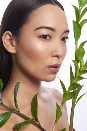 Asian woman looking serious while posing with branch of plant Stock Photo
