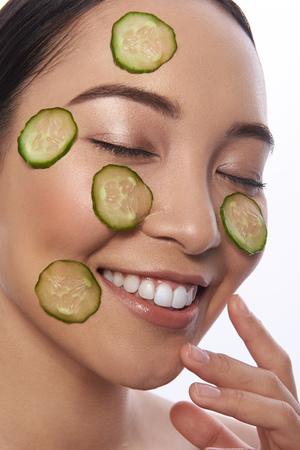 Glad woman enjoying cucumber facial mask and smiling Stock Photo