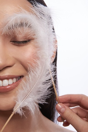 Two fluffy feathers touching the skin of smiling lady Stock Photo
