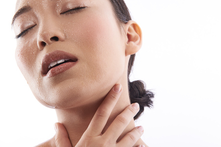 Calm woman having her eyes closed and touching her neck Stock Photo