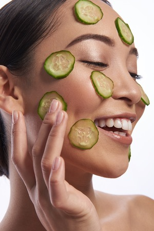 Happy lady with makeup touching cucumber slice on her cheek