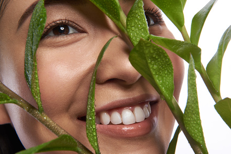 Face of smiling Asian woman behind the green leaves