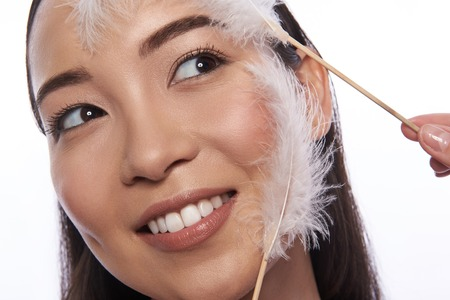 Asian woman and soft feathers touching her skin