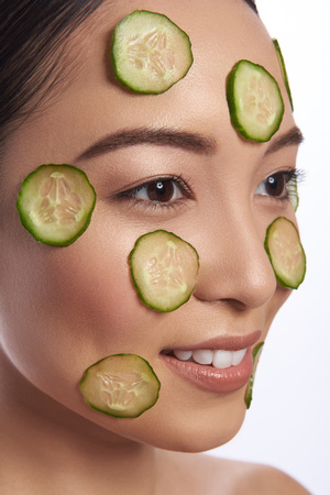Lady with cucumber slices on her face looking away
