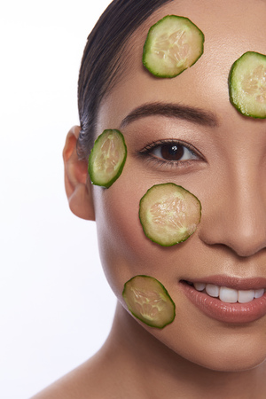 Half face of calm Asian woman with cucumber mask