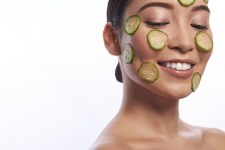 Pretty lady with cucumber mask looking happy and smiling