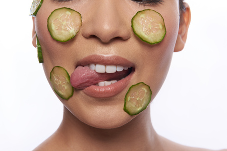 Woman licking slice of cucumber on her cheek Stock Photo