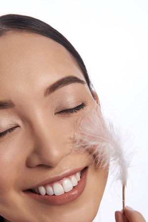 Pleased woman smiling and enjoying feather on her cheek