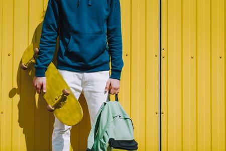 Young hipster man holding skateboard and sack Reklamní fotografie