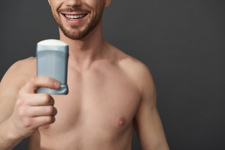 Caucasian guy holding male cosmetics for armpits in hand