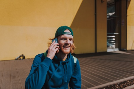 Young hipster man talking by mobile phone
