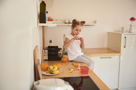 Charming little girl peeling orange in kitchen