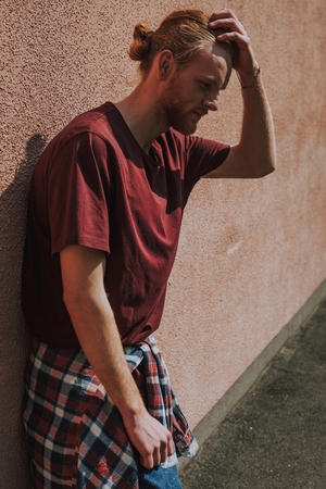 Thoughtful hipster man leaning on building wall