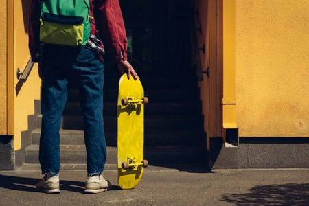 Hipster man with skateboard stay before entrance Stock Photo