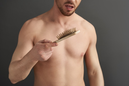 Caucasian guy keeping hairbrush in arm while situating in studio
