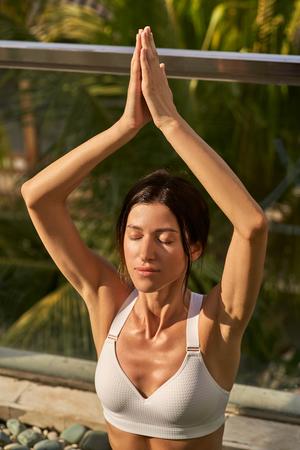 Young woman is enjoying meditation under sun