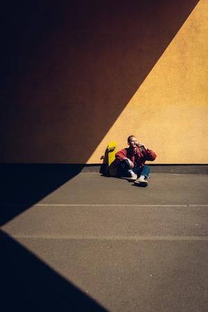 Hipster man drinking coffee sitting on ground