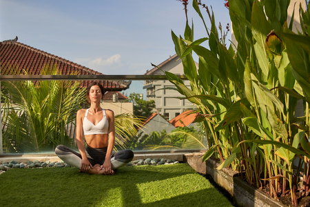Tranquil woman is meditating in open air