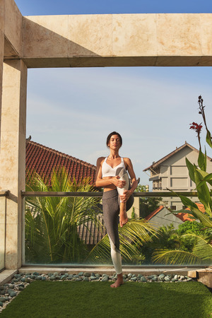 Calm woman is practicing yoga in open air Stock Photo
