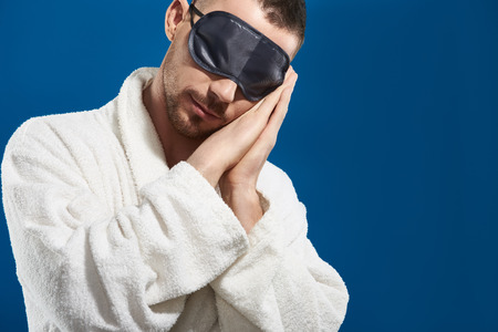 Caucasian young man in night eye patches sleeping against blue background