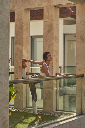 Merry young female is stretching legs on balcony Imagens