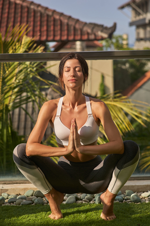 Happy woman is meditating in asana in sun Imagens