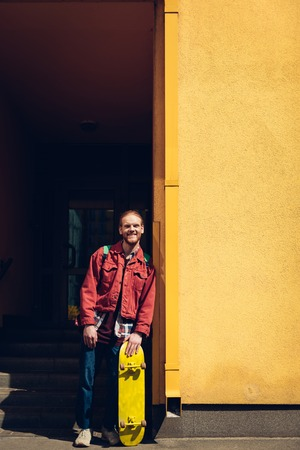 Smiling hipster man staying with yellow skateboard Banco de Imagens - 124919960
