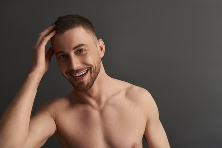 Waist up portrait of muscle handsome bearded young man after having shower