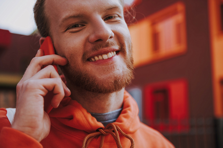 Happy hipster man talking by phone outdoor
