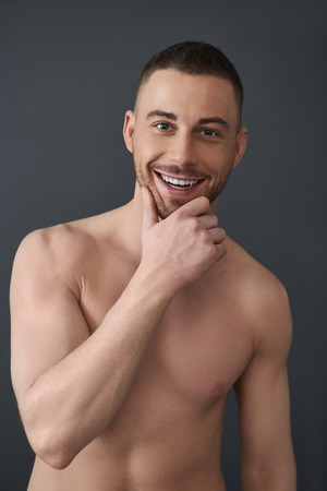 Waist up of muscle handsome bearded young man after having shower Imagens