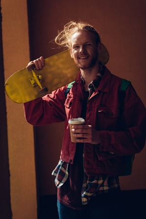 Smiling skater man with coffee and skateboard
