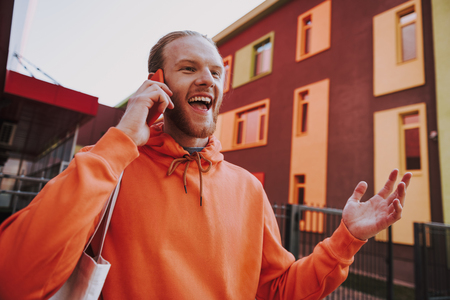 Happy hipster man talking by phone on walk Imagens