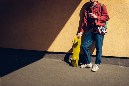 Skater man with coffee leaning on wall