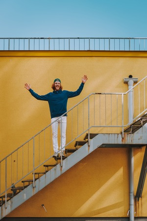 Happy hipster man holding hands up on stairs Banco de Imagens