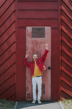Happy excited hipster man on worn out door view Reklamní fotografie