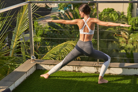 Young woman is practicing pilates on balcony Imagens