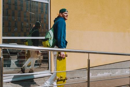 Hipster man with skateboard walking on street