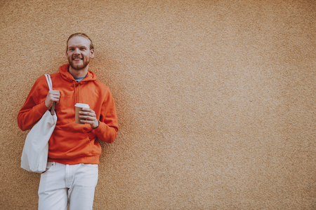 Happy red haired male leaning on wall with coffee