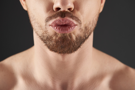 Close up portrait of bearded young man situating against gray background Stock Photo