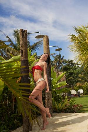 Woman is having shower outside in tropical resort Reklamní fotografie - 124908316