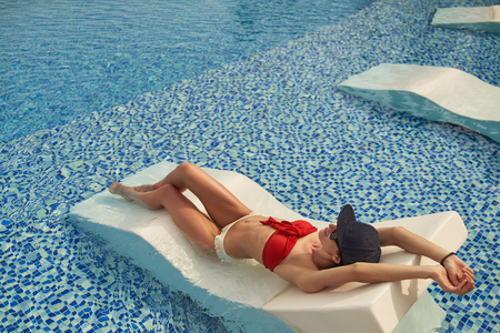 Serene woman is relaxing in swimming-pool outdoor