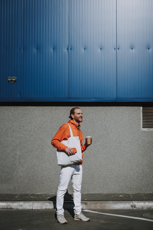 Happy red haired man walking with coffee