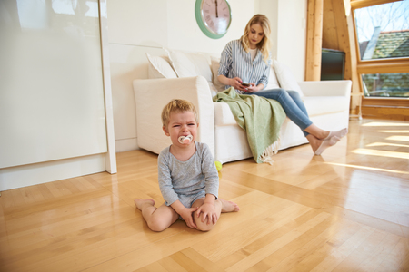 Upset little boy crying while his mother using cellphone