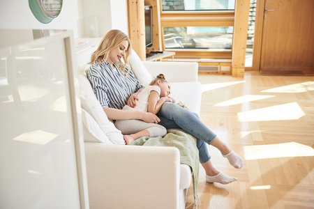 Adorable little girl lying on mother laps at home