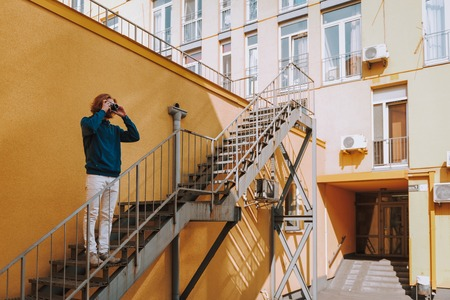 Hipster man making photo on camera on stairs
