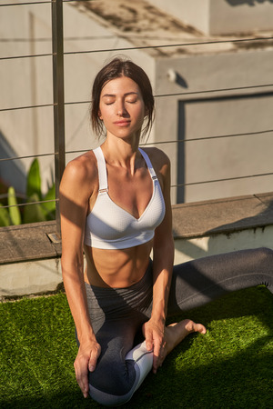 Calm woman is relaxing after workout on balcony Imagens