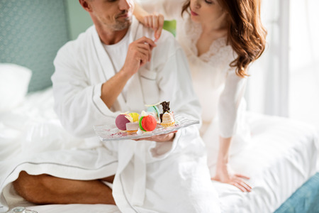Man and woman taking colorful desserts from the glass plate