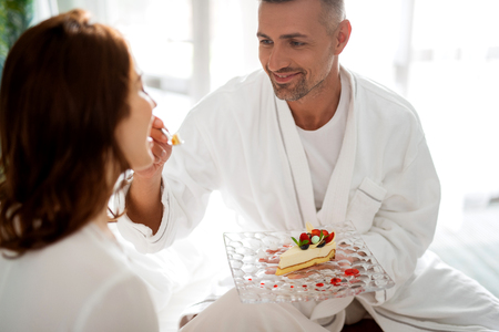 Loving man gently feeding his wife with piece of cake